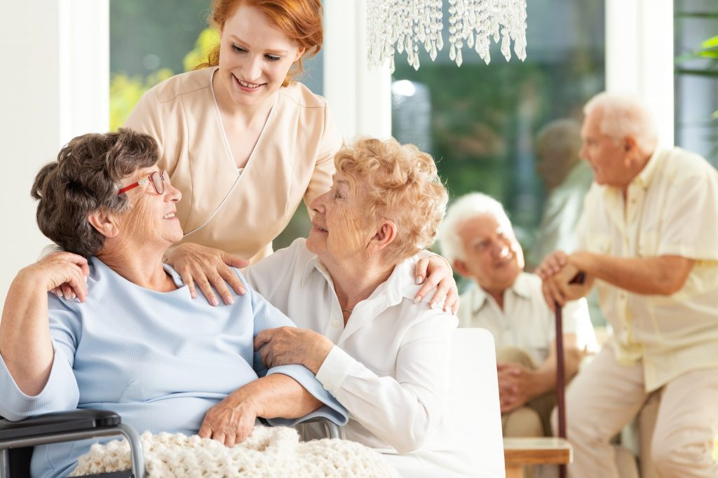 Happy friendship in old age. Tender caregiver standing behind se
