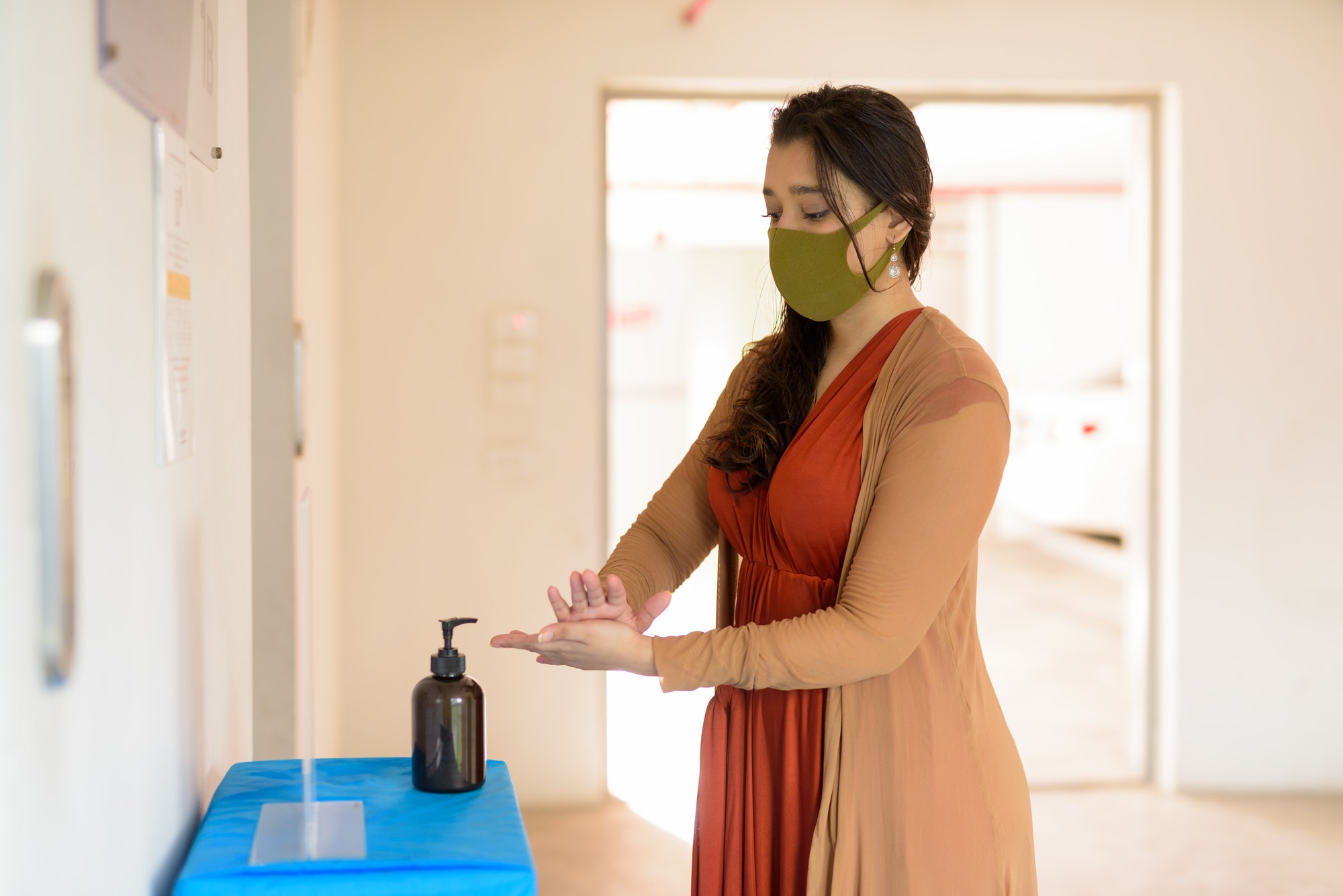 Young Indian woman with mask using hand sanitizer and rubbing hands together